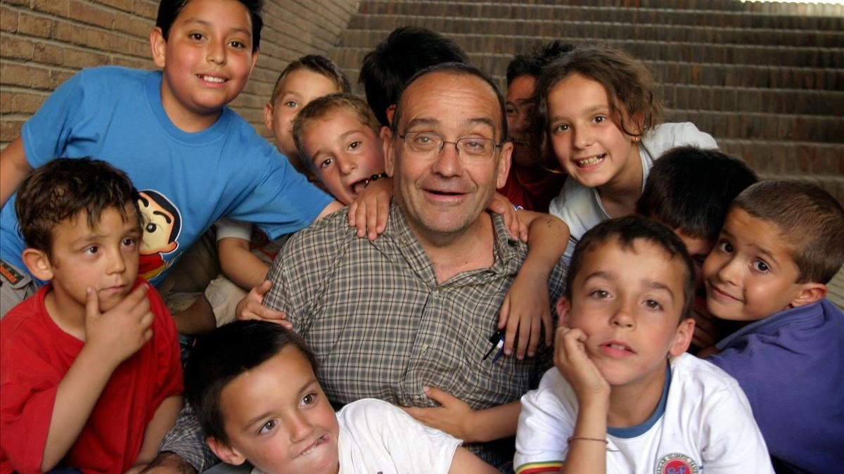 El pare Manel rodeado de niños a los que atendía en Nou Barris, en el 2004.
