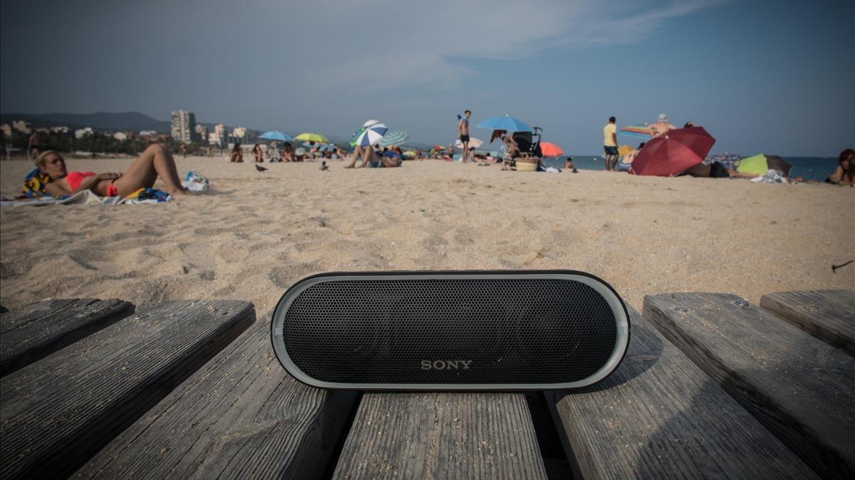 Altavoz autoamplificado con conexión bluetooth con la playa de fondo