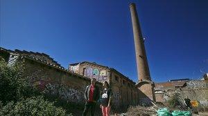 Dos activistas de la plataforma frente a la fábrica abandonada.