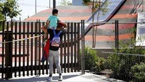 Un padre y su hija observanel recinto del tobogán gigante de Glòries cerrado al público, este mediodía.