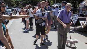 Un hombre que pasea a su perro esquiva el'paloselfi' que esgrimen unas turistas, en Barcelona.