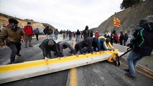 Un grupo de jóvenes mueve un bloque de cemento para crear una barricada en medio del asfalto, en la frontera