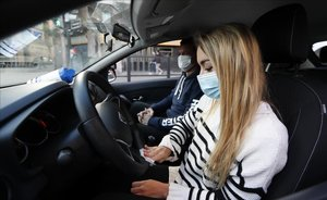 Una alumna de autoescuela junto a su profesor, protegidos con mascarillas, en el coche, en Bilbao.