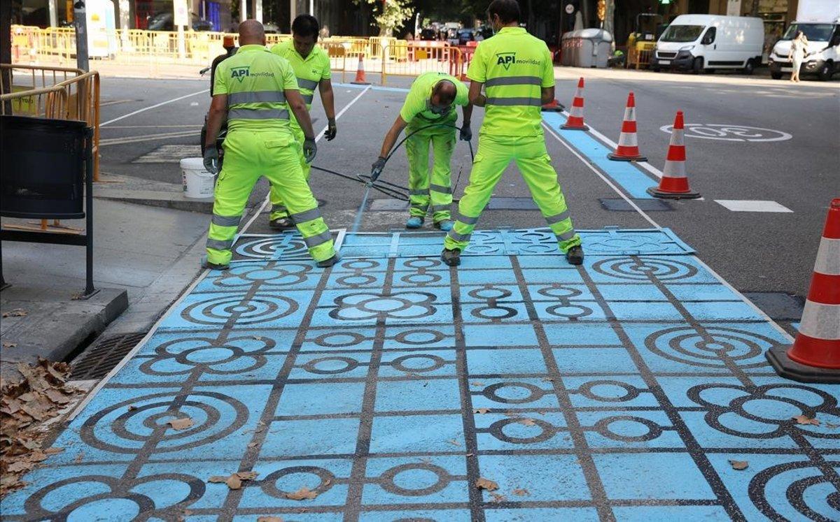 Operarios trabajan pintando en la calle de Rocafort.