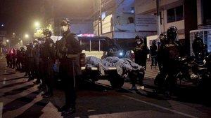 Los cuerpos de algunos de los fallecidos en la discoteca, custodiados por la policia peruana frente al local del accidente.