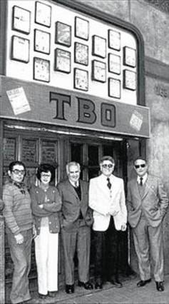 Hoy y ayer 8Rosa Segura, con un antiguo ejemplar del TBO en su casa (arriba). Abajo, en 1983, en la puerta de la revista, con el director, Albert Viña (americana blanca), y el guionista Carles Bech (gafas de sol).