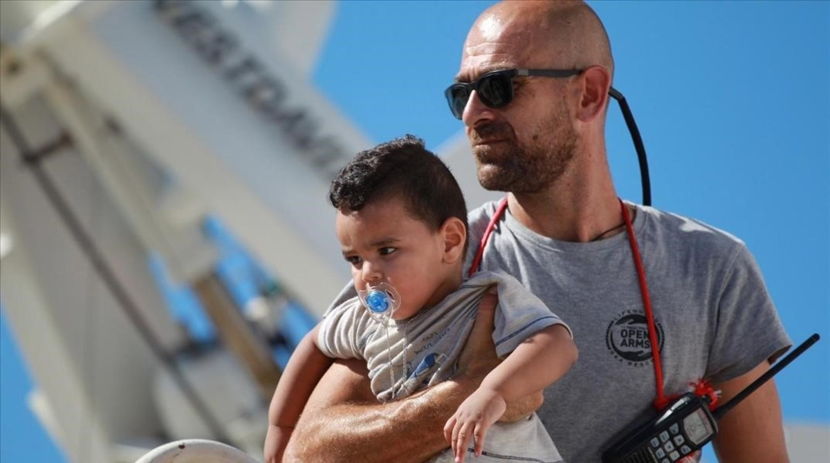 Un voluntario de Open Arms con un niño durante un desembarco en Agirento (Sicilia).