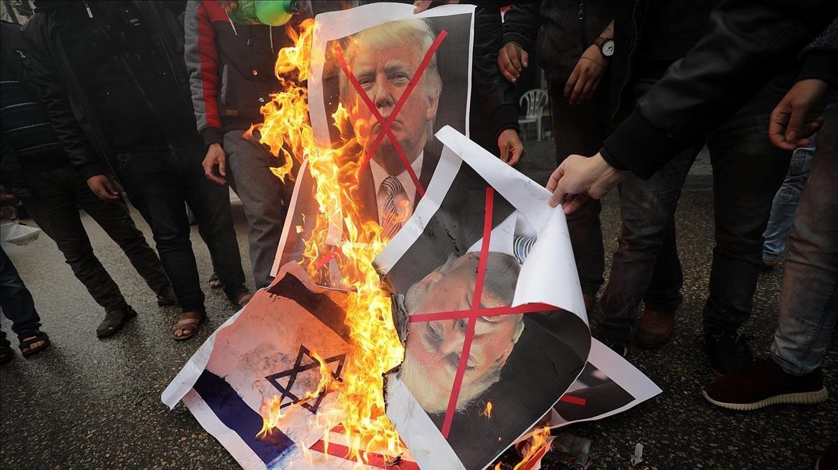 Varios palestinos, contrarios a la decisión de presidente Trump, queman su fotografía y banderas estadounidenses.