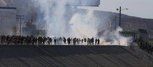 Vista de gases lacrimogenos que la policia fronteriza utiliza para evitar que grupos de personas crucenla garita El Chaparralde la ciudad de Tijuanaen el estado de Baja CaliforniaMexico.EFE David Guzman