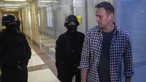 Alexei Navalni, en sus oficinas con dos policías, ayer.