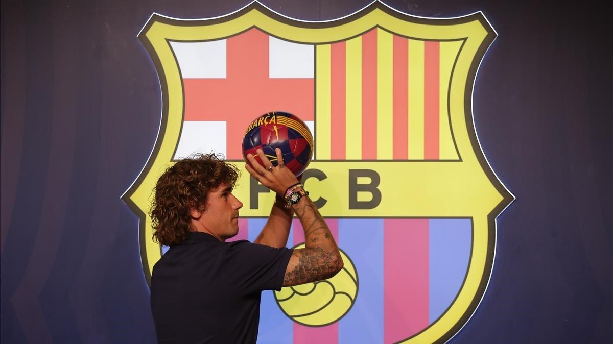 Antoine Griezmann simula tirar a canasta tras el posado protocolario en la tienda del Barça junto al Camp Nou.