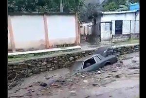 Un carro es arrastrado por una calle tras el desborde del río El Limón.
