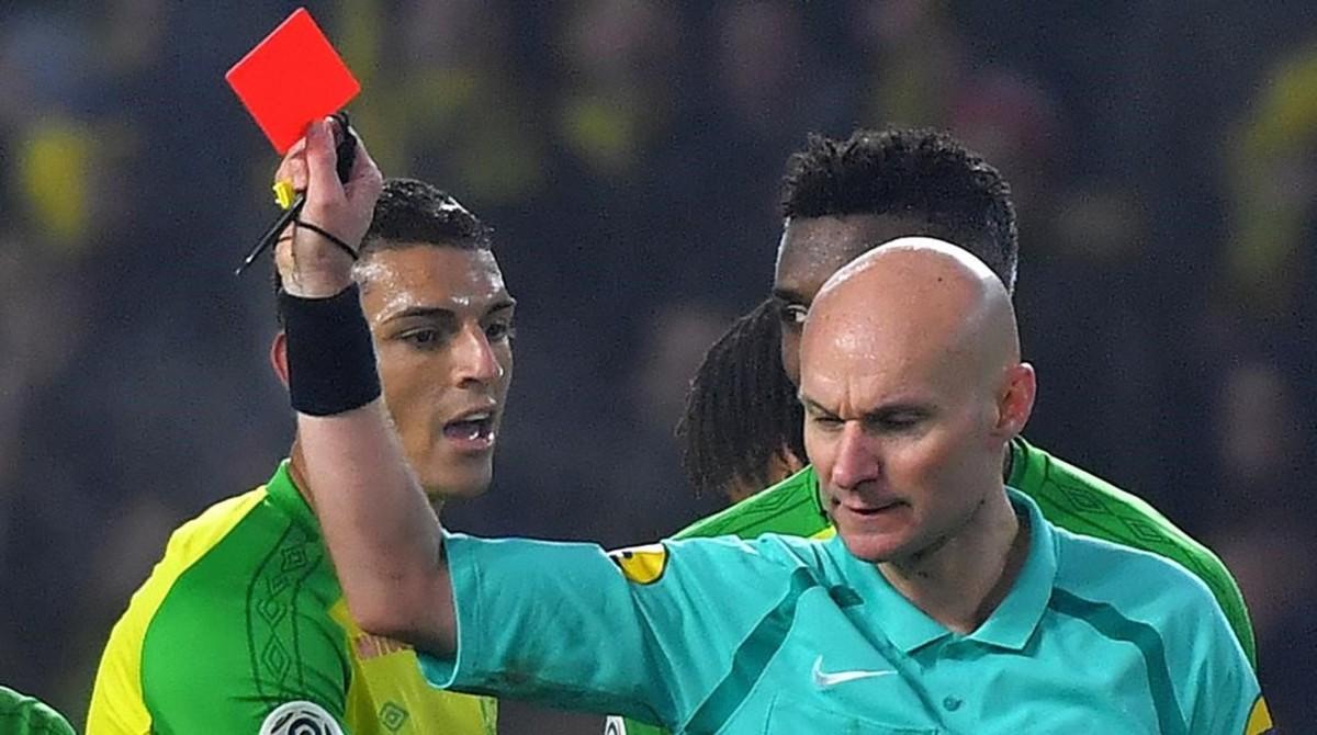El árbitro Tony Chapron muestra la tarjeta roja al defensa brasileño Diego Carlos, del Nantes.