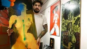 El artista Santiago Benítez muestra uno de sus cuadros pintarrajeado con spray.