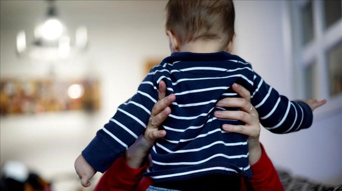 Una madre juega con bebéjuega en su casa.