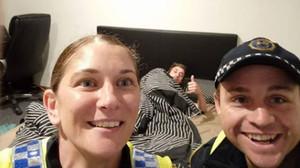 Dos policies es fan un 'selfie' amb un jove borratxo després de portar-lo a casa i ficar-lo al llit