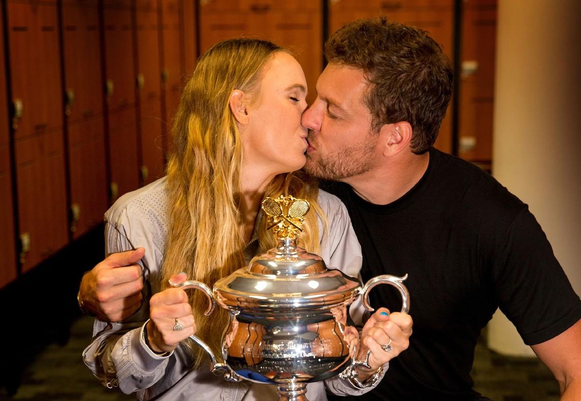 Caroline Wozniacki besa a su compañero David Lee, exjugador de los Spurs (NBA), con la copa como testigo.