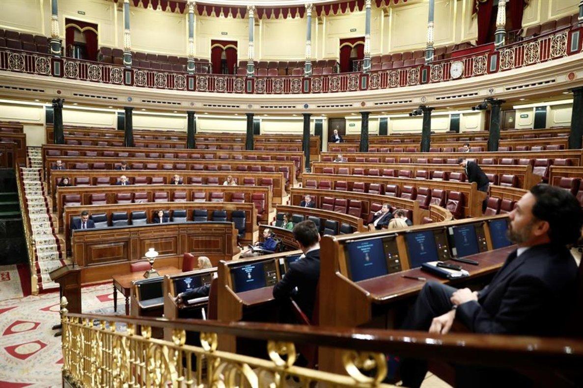 Diputados colocados en sus escaños del Congreso, donde este miércoles el presidente del Gobierno, Pedro Sánchez, explica la declaración del estado de alarma y las medidas para paliar las consecuencias de la pandemia provocada por el coronavirus, en Madrid (España), a 18 de marzo de 2020.