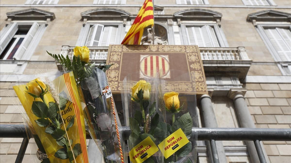 Fachada del Palau de la Generalitat con ramo de rosas amarillas en primer plano.