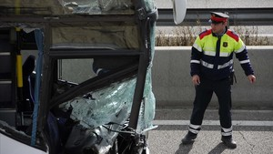 Un agente de los Mossos dEsquadra observa un autocar que ha chocado con un camión en Tárrega.
