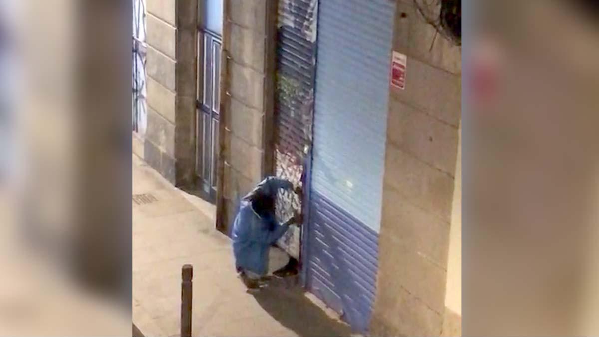 Un hombre intenta forzar la puerta de un bajo abandonado en el Raval.