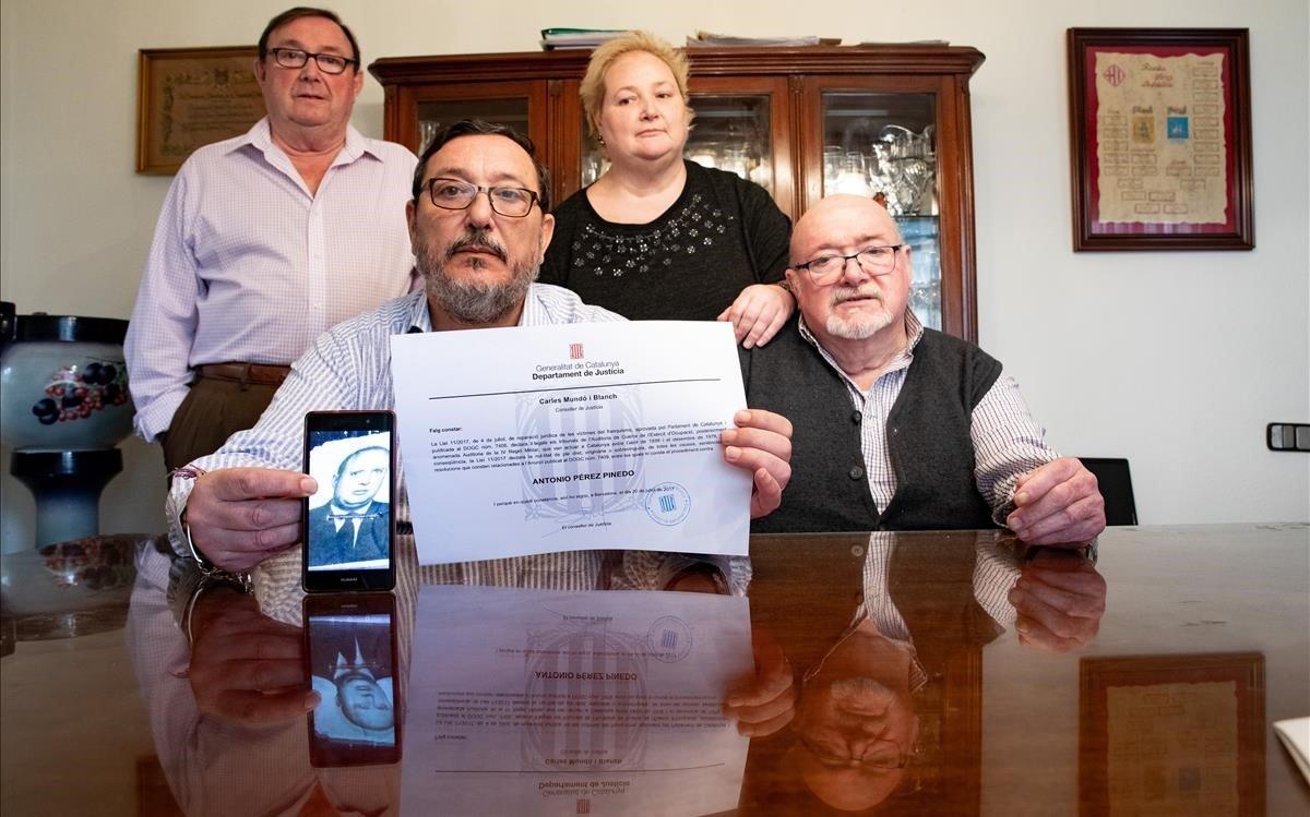 Antonio, Fernando, Carmen y Francisco Pérez (de izquierda a derecha) muestran el diploma de rehabilitación de su padre.