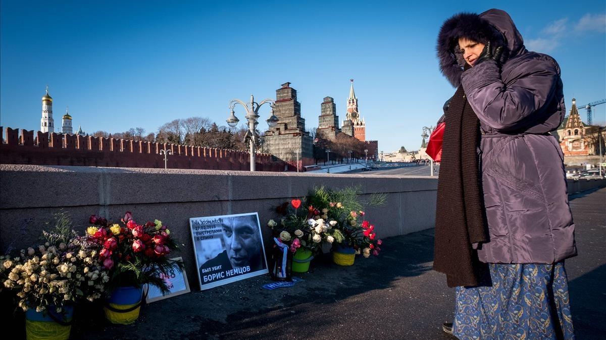 Una mujer observa las flores colocadas en el lugar donde fue asesinadoBorisNemtsovenMoscú.