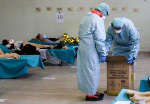 Personal sanitario atiende a enfermos de coronavirus en un hospital de campaña en Brescia (Italia).