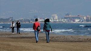 Personas paseando por la playa de Valencia este sábado.