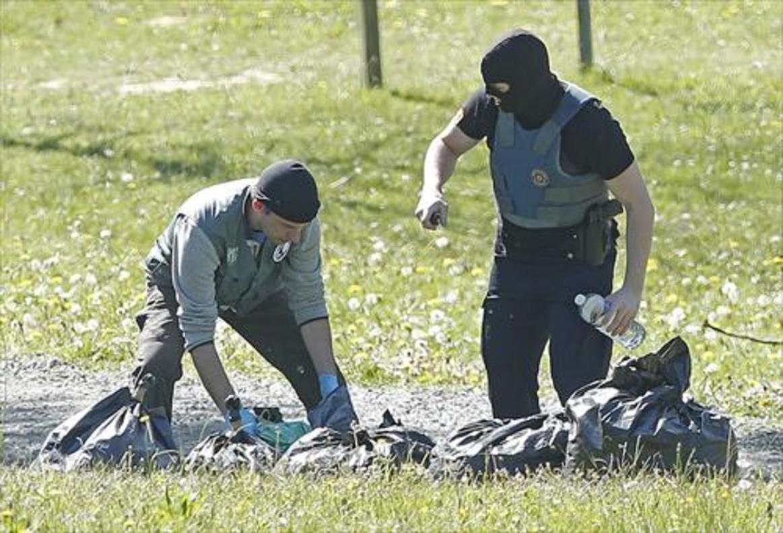 Policías franceses examinan las armas de uno de los zulos de ETA.