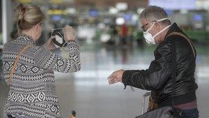 Una pareja se colocan las protecciones en la T-1 del aeropuerto del Prat.