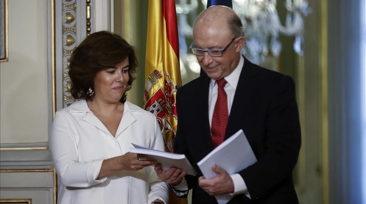 La vicepresidenta Santamaría y el ministro Montoro, con el informe sobre la financiación autonómica elaborado por un grupo de expertos, el pasado 27 de julio.