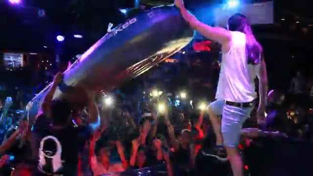 Steve Aoki lanza una barca sobre los espectadores de la sala Opium de Barcelona en el 2014. Luego se encarama a ella una colaboradora.