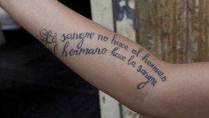 Una frase tatuada en un brazo.