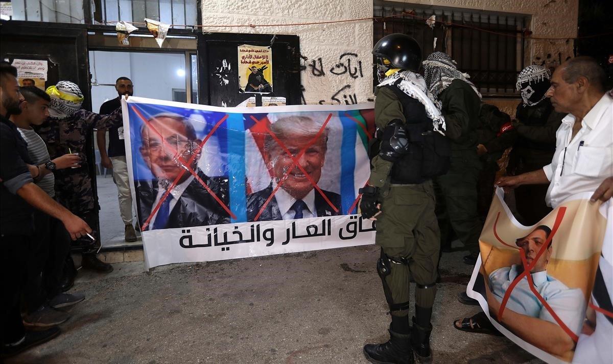 Unos palestinos se disponen a quemar imágenes de Mohamed bin Zayen, Binyamin Netanyahu y Donald Trump, tras conocerse el pacto entre Emiratos Árabes Unidos e Israel.