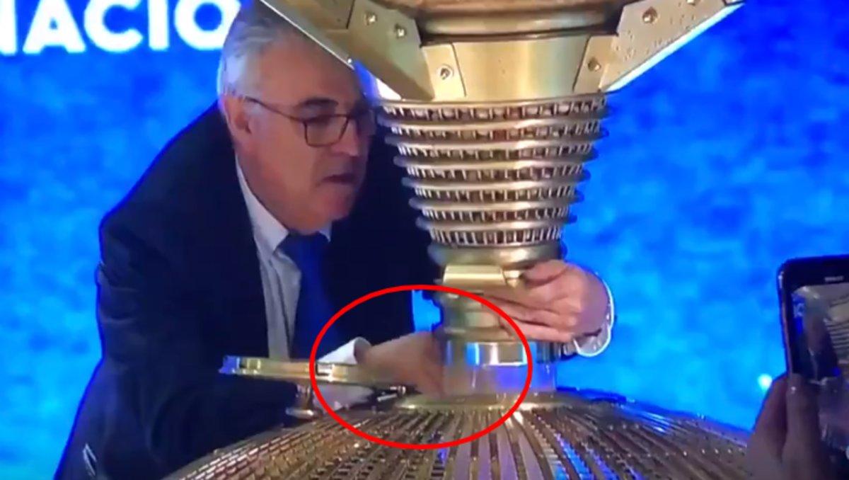 Vídeo en el que se puede ver cómo el el operario de Loterías del Estado, que lleva algo sujeto en su mano derecha, la abre y lo deja caer en el bombo