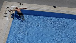Una persona toma el sol en una piscina.