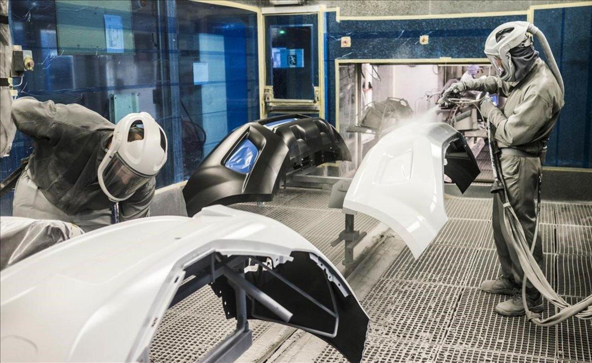 Dos operarios trabajan en la planta de pintura de la fabrica de Nissan en la Zona Franca de Barcelona.