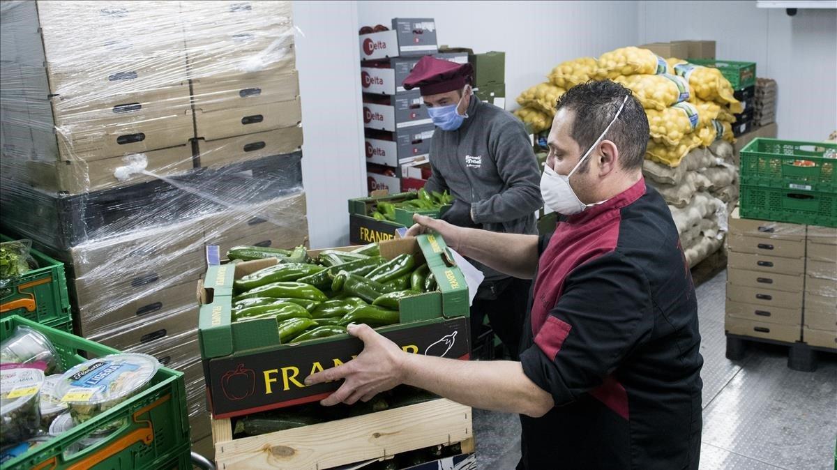 Jordi e Ignasi distribuyen las cajas de verduras frescas en el almacén de FiT, en Barcelona