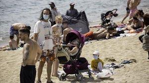 Una familia llega a unaplaya de la Barceloneta con la mascarilla puesta, durante el primer día de obligatoriedad de tapabocas en todos los espacios públicos de Catalunya.