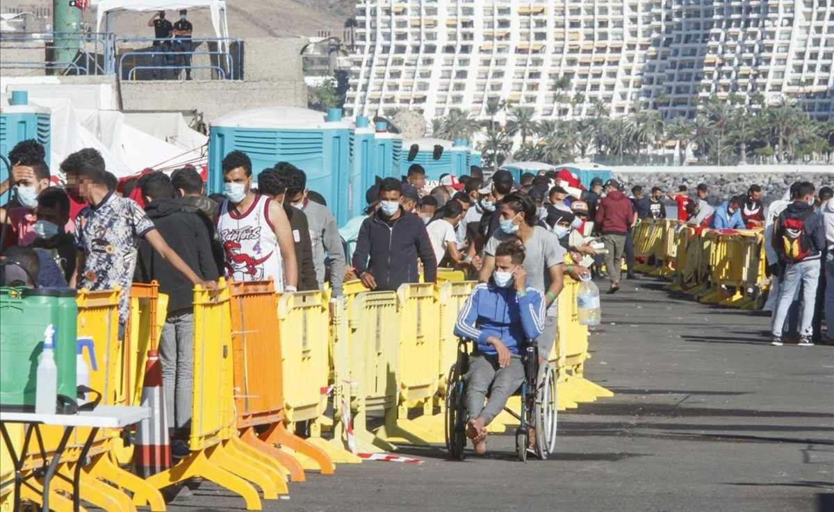 Varios inmigrantes hacen cola en el Muelle de Arguineguínen Gran CanariaCanarias.