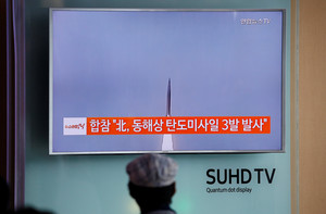 A passenger watches a TV screen broadcasting a news report on North Korea firing three ballistic missiles into the sea off its east coast, at a railway station in Seoul