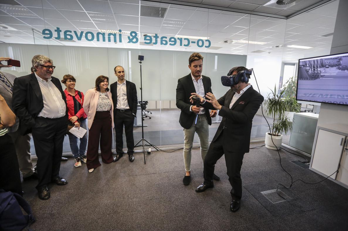 El alcalde de Cornellà, AntoniBalmón, primero a la izquierda y la presidente de Siemens España, Rosa García, cuarta por la derecha, asisten a una demostración de usos de realidad virtual en la industria en las nuevas instalaciones de Siemens.