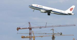 Un avión de Air China sobrevuela grúas en Pekín.