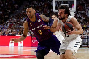 El base madridista Sergio Llull controla el balón presionado por la defensa de Adam Hanga.