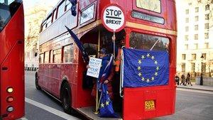 Un activista anti-'brexit' muestra una bandera de la UE en un autobús de Londres.