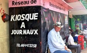 Un hombre sentado delante de un quiosco cerrado en Guinea.