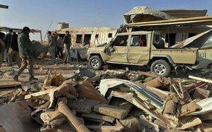Combatientes de la milicia de Kataeb Hezbollah inspeccionan la destrucción de su cuartel general después de un ataque aéreo estadounidense en Qaim, Irak.