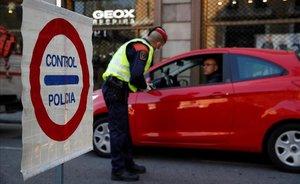 Mossos d'Esquadra hacen controles de coches en el centro de Barcelona para velar por el cumplimiento del confinamiento.