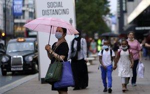 Una persona con mascarilla en las calles de Londres.